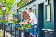Romantic couple on the balcony decorated with flowers. On Montmartre, Paris Stock Photos