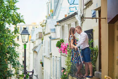Romantic couple on the balcony decorated with flowers. On Montmartre, Paris Stock Photo
