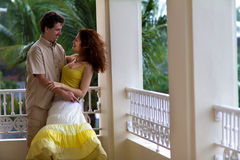Romantic couple on a balcony in a tropical rain. Romantic young couple on a balcony in a tropical rain Royalty Free Stock Images