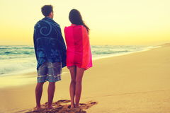Romantic couple bathing with towels on beach sunset Stock Photos