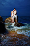 Romantic couple at beach. Outdoor portrait of young romentic couple in white cotton clothes sitting on stone with waves around at night beach of Phuket island stock images