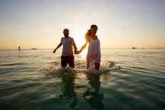 Romantic couple on the beach at colorful sunset on background.  Stock Images