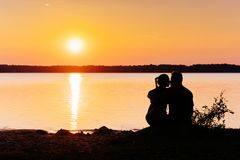 Romantic couple on the beach at colorful sunset on background.  Stock Photography