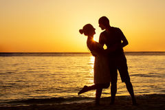 Romantic couple on the beach at colorful sunset Royalty Free Stock Photos