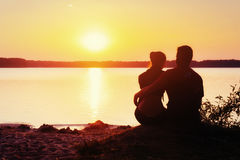 Romantic couple on the beach at colorful sunset background royalty free stock image