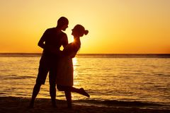 Romantic couple on the beach at colorful sunset on background.  Royalty Free Stock Photography