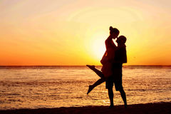 Romantic couple on the beach at colorful sunset. On background Stock Image