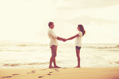 Romantic Couple on the Beach at Sunset. Stock Photo