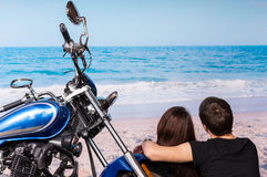 Romantic couple at the beach with their motorbike Royalty Free Stock Photos