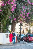 Romantic couple in bright clothes and sunglasses holding hands, smile and standing under blooming tree on the street. Happiness, l royalty free stock photos