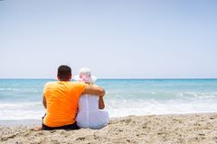 Romantic couple in casual clothes sitting on the sandy beach and looking to sea.  royalty free stock photos