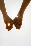Romantic couple with clasped hands. Backlit by a bright morning sunburst in a closeup conceptual image of love and friendship Royalty Free Stock Image