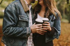 Romantic couple with coffee walking outdoors in the autumn park Stock Photos