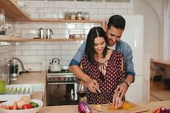 Romantic couple cooking in kitchen at home. Shot of romantic young couple chopping vegetables together in kitchen. Young men and women cooking food together at Stock Photo