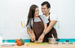 Romantic couple is cooking on kitchen. Young happy smiling couple  while making salad at home. Hobby, Healthy lifestyle concept stock image