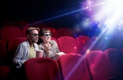 Romantic couple sitting at spectacle. Romantic couple cuddling and watching the miraculous part of the film Stock Photo