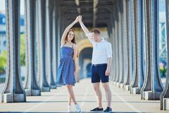 Couple walking along Bir-Hakeim bridge in Paris, France. Romantic couple dancing on Bir-Hakeim bridge in Paris, France Stock Image