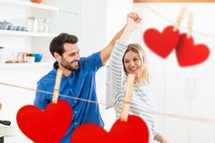 Romantic couple dancing at home. Composite image of red hanging hearts and romantic couple dancing at home Royalty Free Stock Images