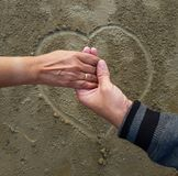 Romantic couple on date holding hands on heart sign background drawn on wet beach sand royalty free stock image