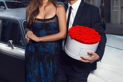 Romantic couple date. Man and woman with rose flowers wearing suit and dress standing near luxury car in the city. stock photography