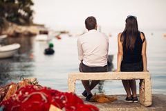 Romantic couple on a date in nature,sitting on the bench looking at serene ocean scene.People living on the coast lifestyle. Fishing town couple dating Stock Images