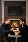 Romantic couple dating. Young romentic couple dating, sitting in front of fireplace at home, drinking red wine stock image