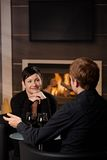 Romantic couple dating. Young romantic couple dating, sitting in front of fireplace at home, drinking red wine royalty free stock photo