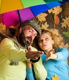 Romantic couple dating. Hipster with beard and cheerful girl expect rainy weather hold colorful umbrella. Couple in love. Lay on wooden background top view royalty free stock photo