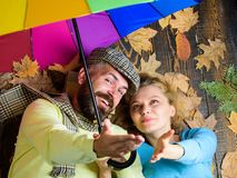 Romantic couple dating. Hipster with beard and cheerful girl expect rainy weather hold colorful umbrella. Rainy weather. Not obstacle for them. Couple in love royalty free stock image