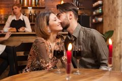 Romantic couple dating in a vintage restaurant. Handsome men kissing gently his girlfriend cheek stock photography