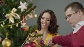 Romantic couple decorating Christmas tree, enjoying mutual pastime at home stock footage