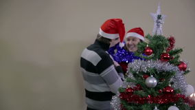 Romantic couple decorating Christmas tree and having fun stock footage