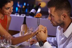 Romantic couple at dinner table. Attractive loving couple holding hands at dinner table, looking affectionate Stock Image