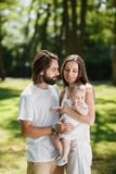 Romantic couple dressed in white stylish clothes is staying in the park and holding their charming little baby in the stock photography