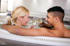 Romantic couple drinking cahmpagne in hot tub Stock Image