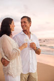 Romantic Couple Drinking Champagne on the Beach at Sunset stock image