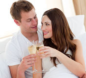 Romantic couple drinking champagne lying in bed Royalty Free Stock Photography