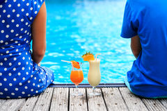 Romantic couple drinking cocktails near pool or Stock Photos