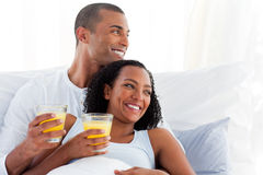 Romantic couple drinking orange juice Stock Photos