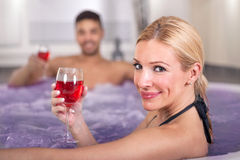 Romantic couple drinking red wine in hot tub Stock Image