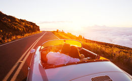 Romantic Couple Driving on Beautiful Road at Sunset Royalty Free Stock Photography