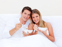 Romantic couple eating cereals lying in bed Stock Photo