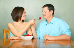 Romantic Couple Eating Fruits On Kitchen Table Stock Images