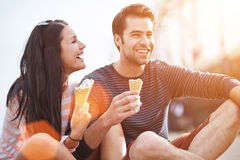 Romantic couple eating ice cream at park. Photo of a romantic couple eating ice cream at park at sunset stock image