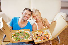 Romantic couple eating pizza at home Stock Images