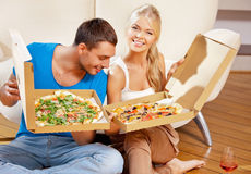 Romantic couple eating pizza at home. Picture of happy romantic couple eating pizza at home (focus on man Royalty Free Stock Images