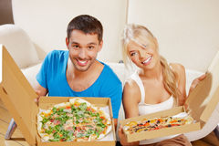 Romantic couple eating pizza at home. Picture of happy romantic couple eating pizza at home (focus on man Royalty Free Stock Photography