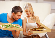 Romantic couple eating pizza at home. Picture of happy romantic couple eating pizza at home (focus on man Stock Photography