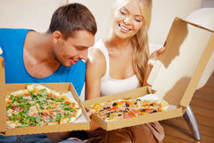 Romantic couple eating pizza at home. Picture of happy romantic couple eating pizza at home (focus on man Royalty Free Stock Photos