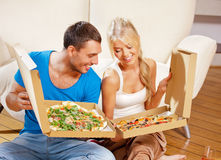 Romantic couple eating pizza at home. Picture of happy romantic couple eating pizza at home (focus on man Royalty Free Stock Image